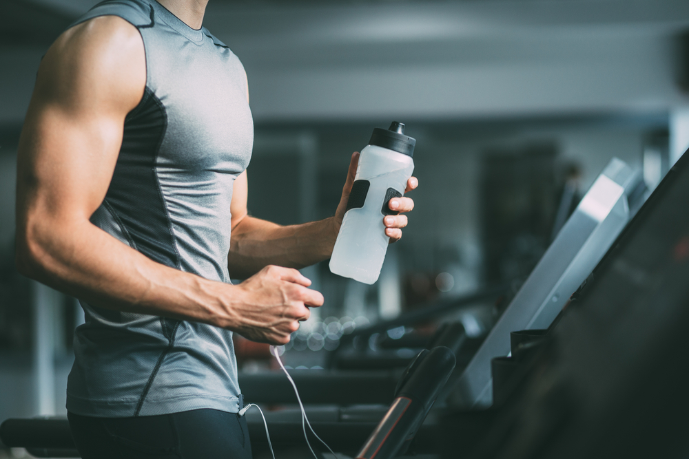 Man on a treadmill holding a bottle of water.