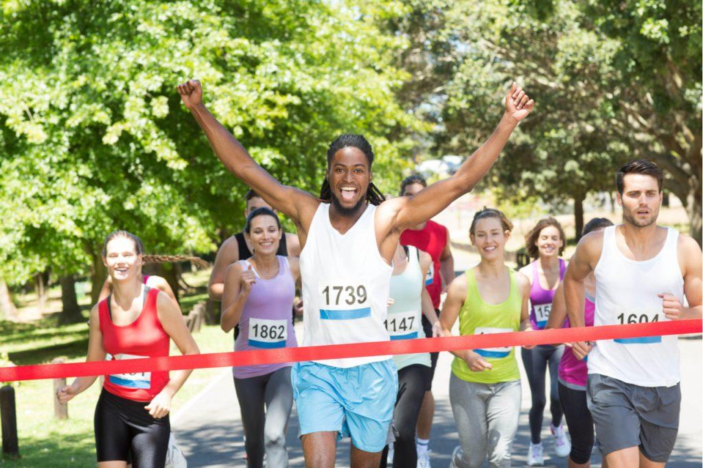 A man celebrating a win from a marathon who experienced eustress vs distress.