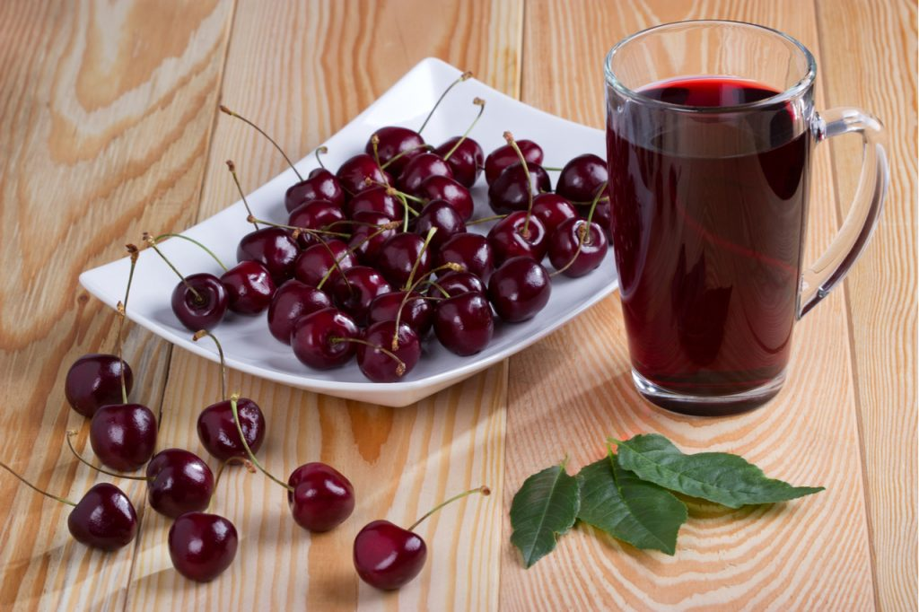A plate of tart cherry next to a glass of its fresh juice.