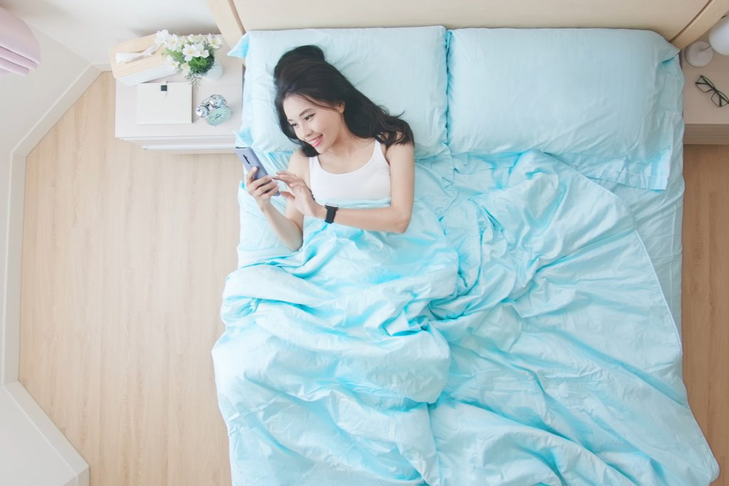 Woman using cellphone while in bed, looking like sending text messages.
