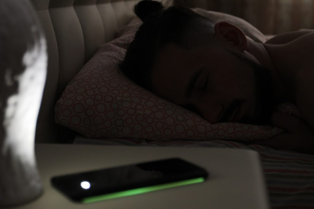 A man sleeping with his phone turned off.