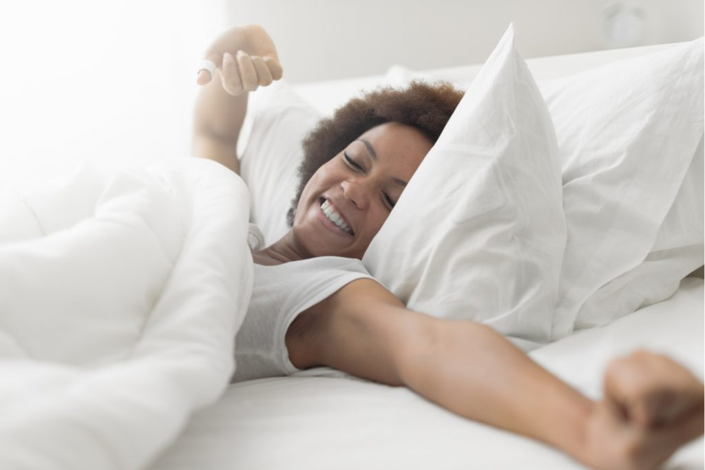 A beautiful woman waking up smiling after a good night's sleep.