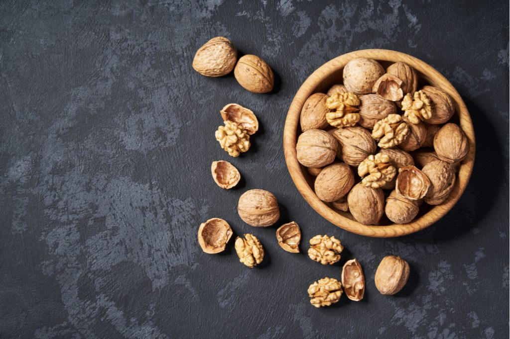 A bowl of walnuts in a black background.