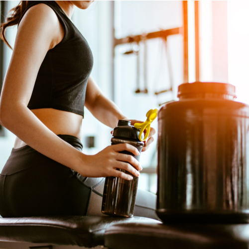 A woman preparing her whey protein drink in a bottle shaker next to the whey protein jar.