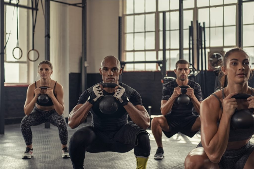 A group of multi color people working out using a kettlebell.