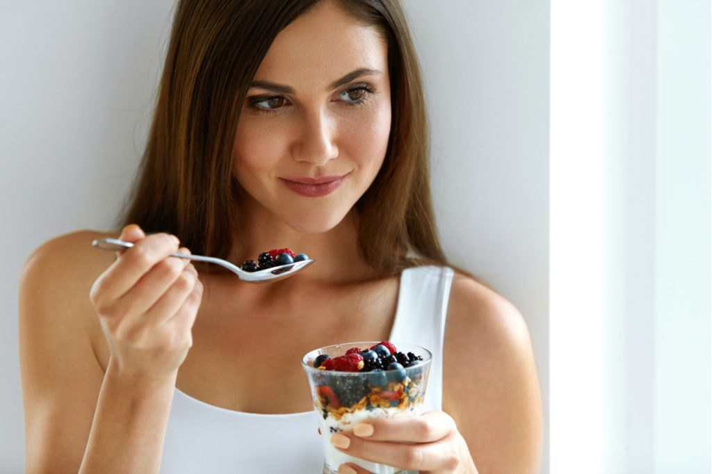 Fit woman holding a cup of overnight oats and a spoon with berries .