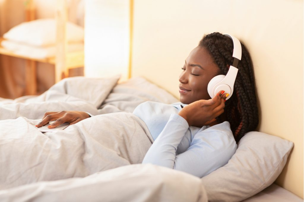 Woman listening to podcast while in bed as a morning ritual.