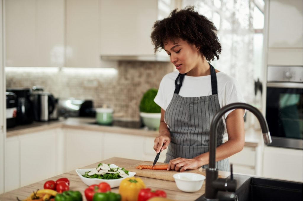 Woman preparing her own vegetarian meal.