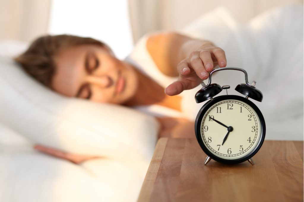 Woman stretching arm to alarm clock after waking up in the morning. What is your morning ritual?