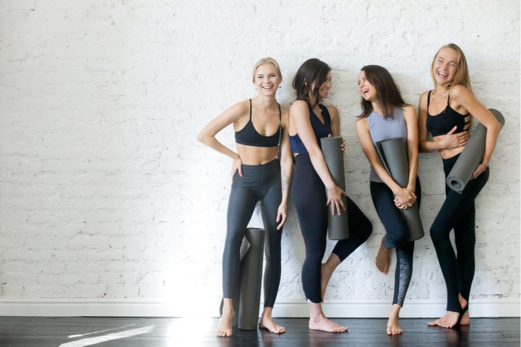Women in eco-friendly clothing holding yoga mats.