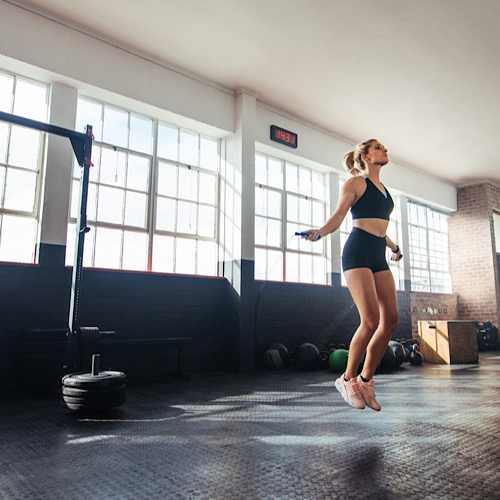 A fit woman training, using a jump rope.