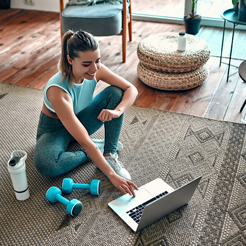 A fit woman sitting on the carpet at home while on her laptop with a tumbler and dumbbells on her side.