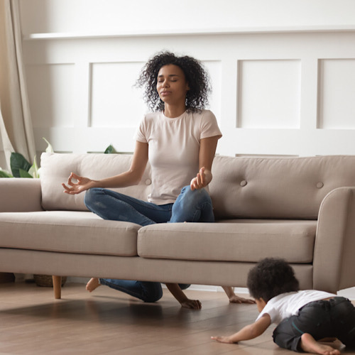 A woman meditating on her couch while her son is on the floor crawling.