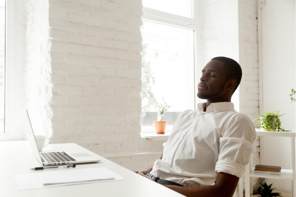 Man relaxing after work breathing fresh air sitting at home office desk with laptop.