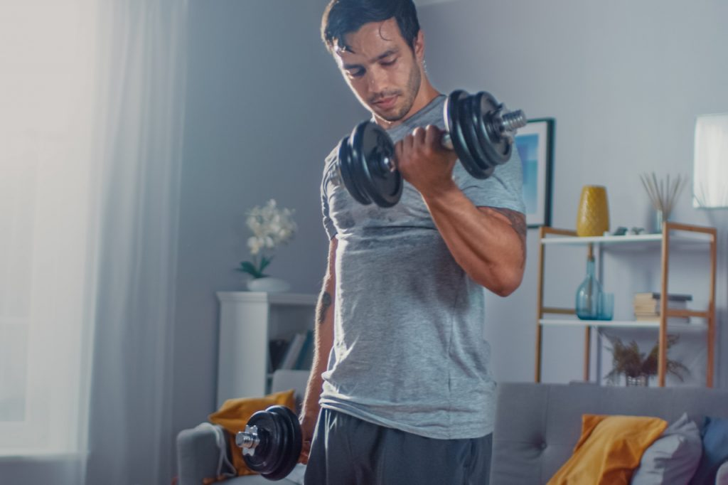 A man lifting dumbbells at home.