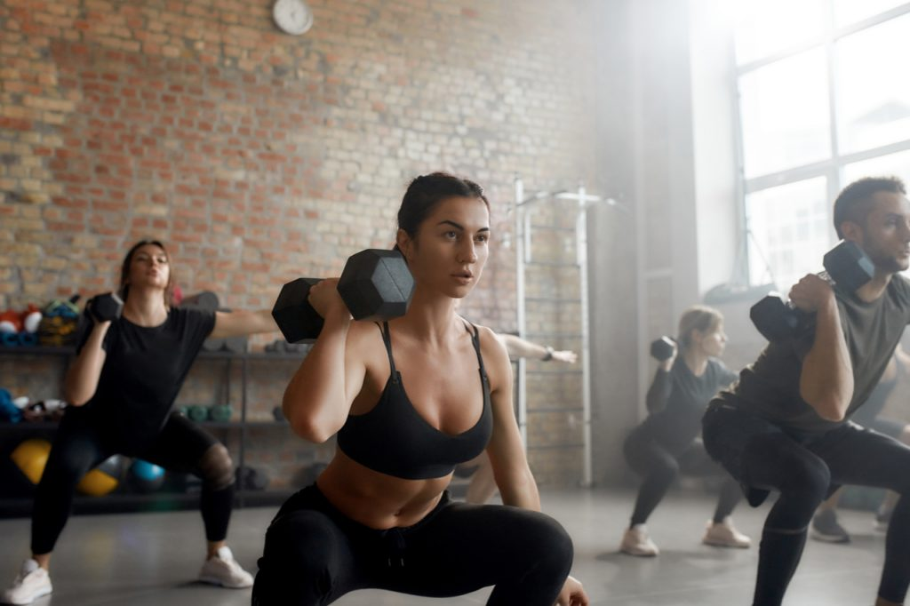 A group doing hiit with dumbbell