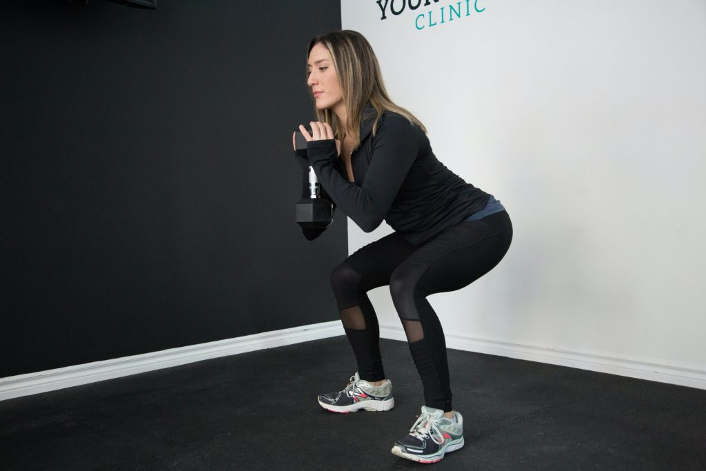 A woman doing a dumbbell workout at home.