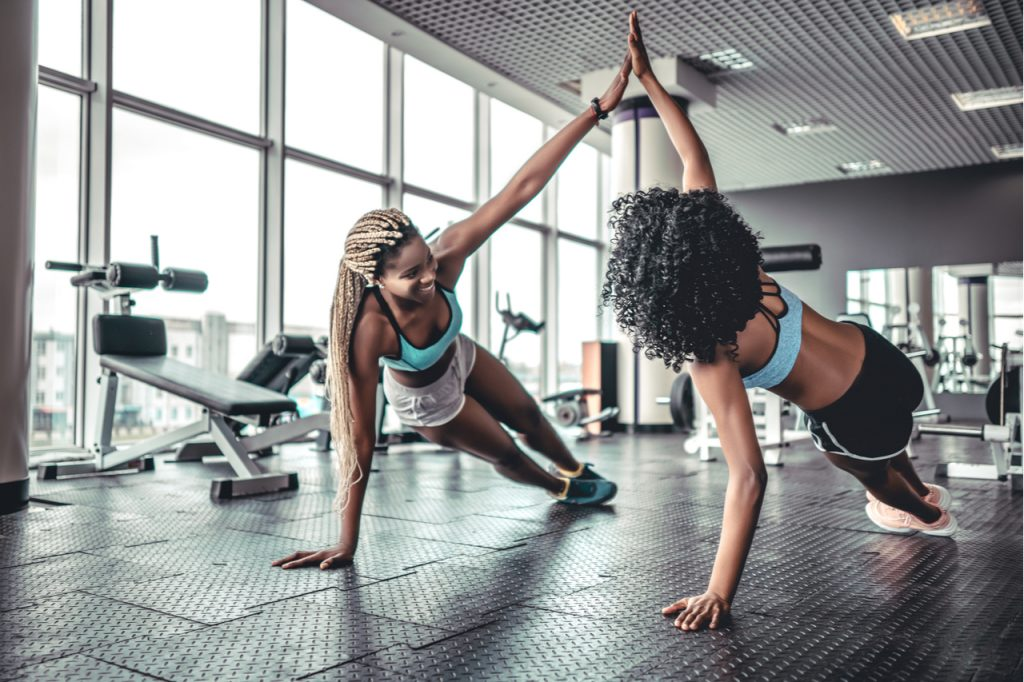 Sporty women giving high fives at the gym while working out.