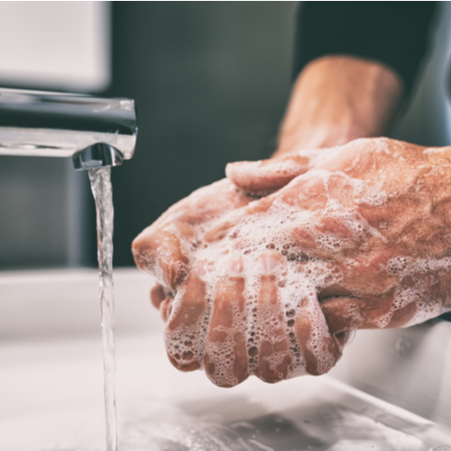 A man doing hand-washing with the water flowing from the faucet.
