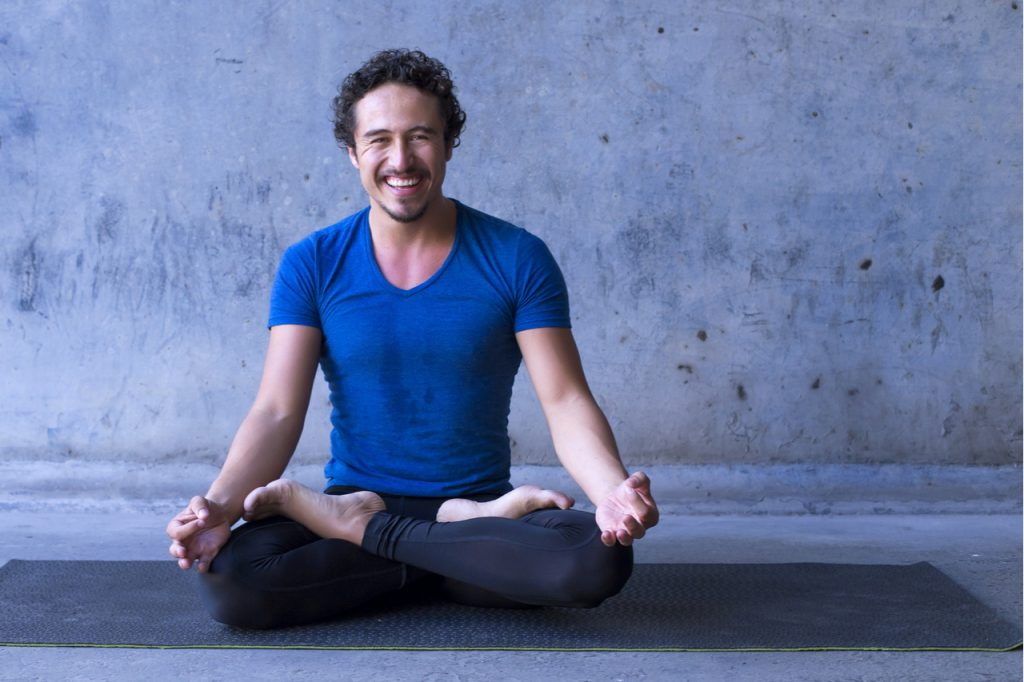 A man smiling happily while doing yoga.