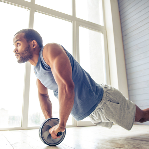 A fit man doing wheel rollouts exercise at home.