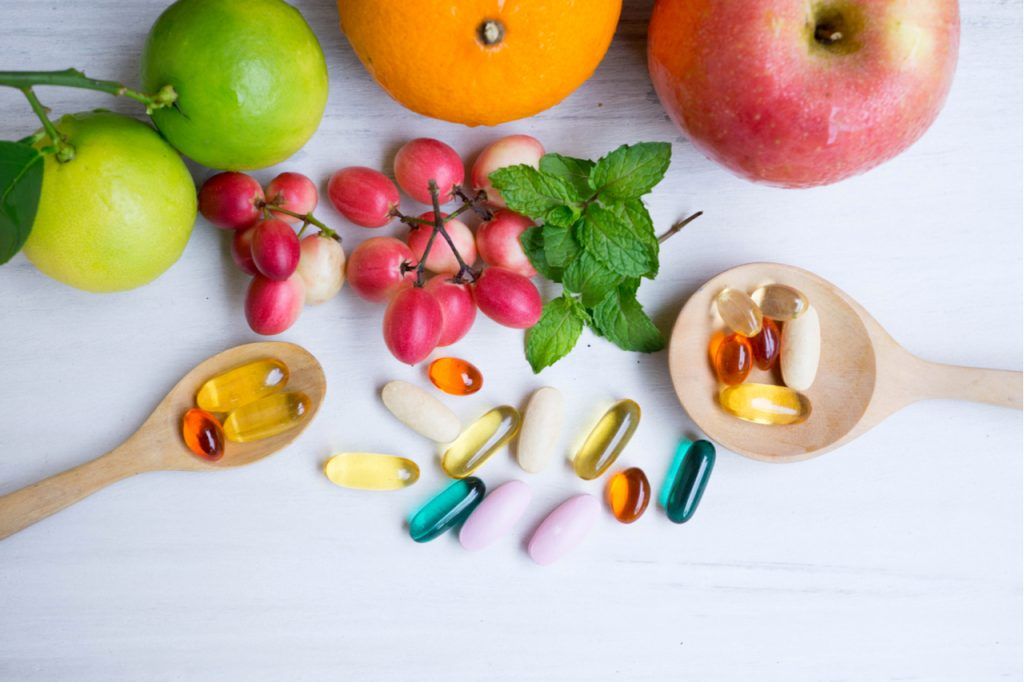 Multivitamin supplements from fruit on white wood background with wooden spoon.