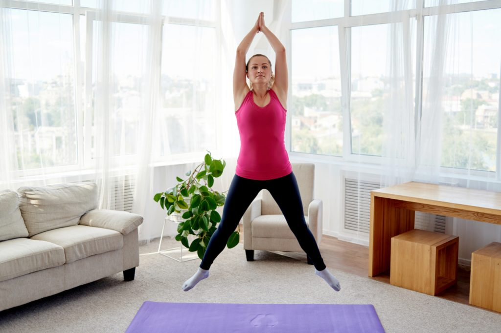 A woman doing jumping jacks in her living room.