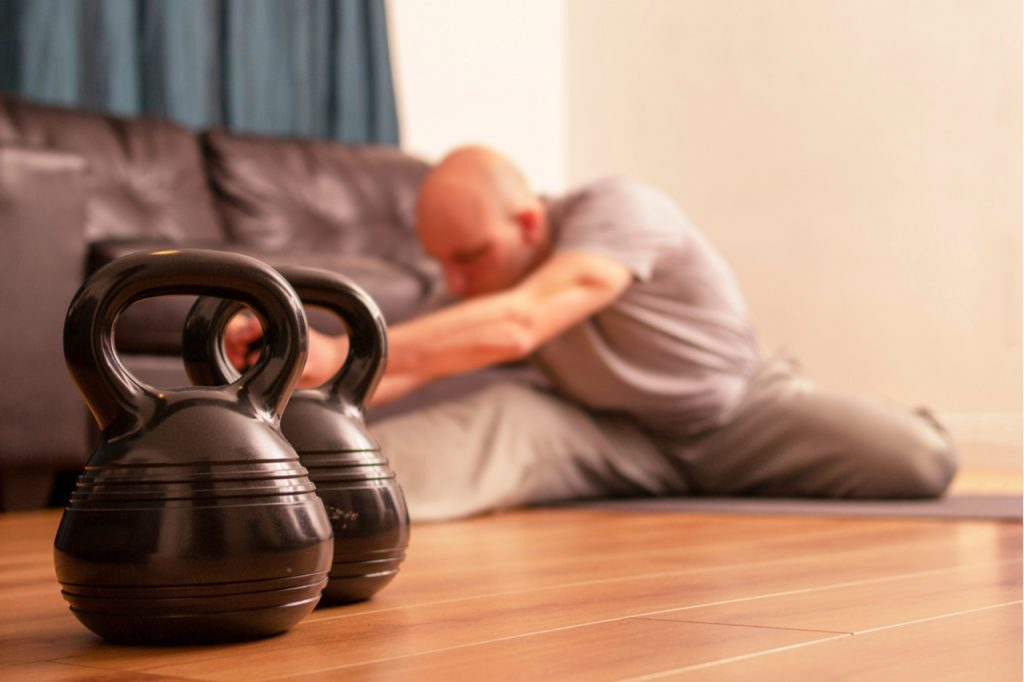 A man doing workout in his living room next to his kettlebell.
