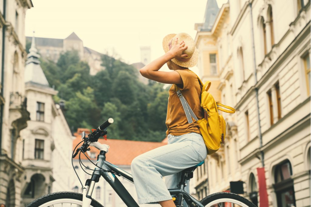 A woman student riding a bike looking for cheapest places travel.