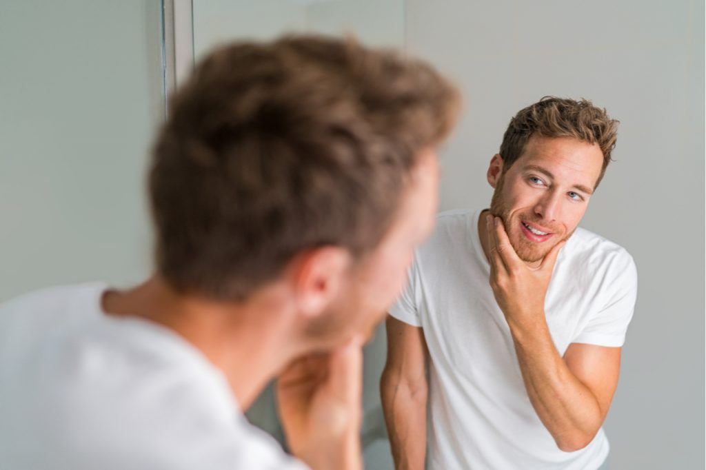 Man looking at the mirror, feeling good about himself being clean.
