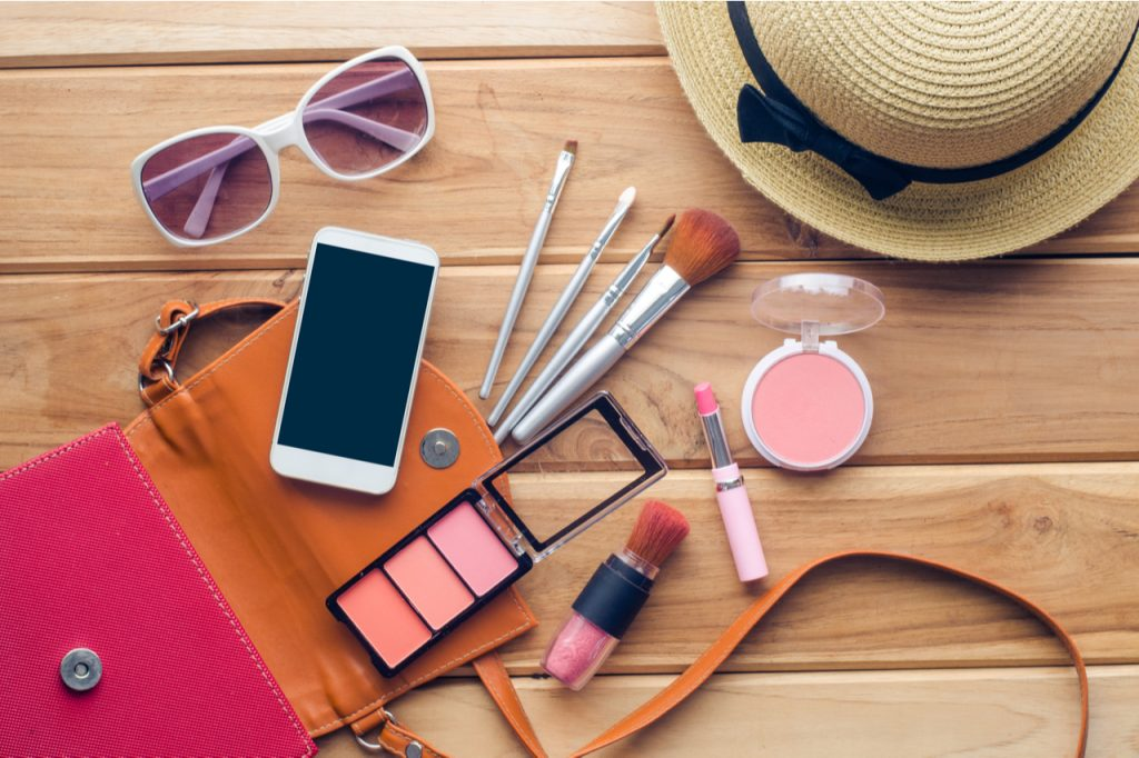 An image of a pink bag with beauty products, a phone, a hat and a sunglasses.
