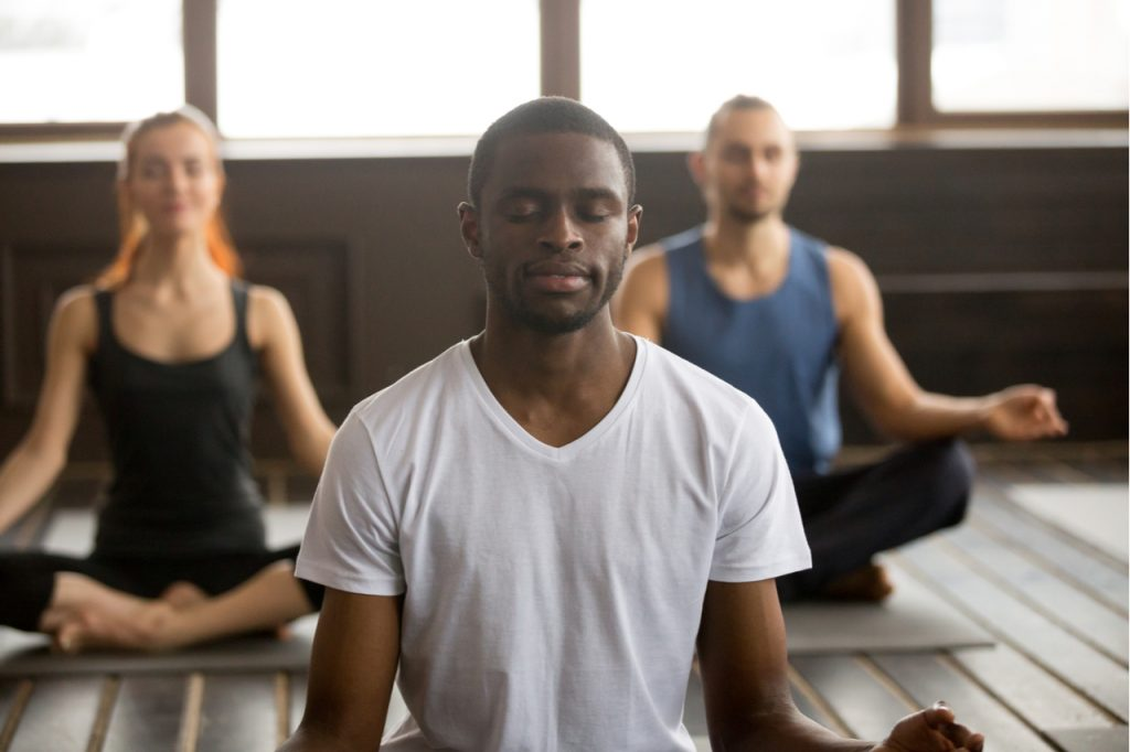 A group of people meditating as part of self-care.