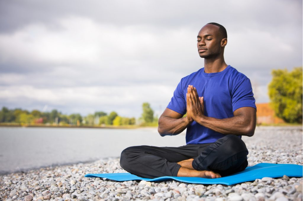 A man wearing athletic wear sitting on the beach exercising yoga