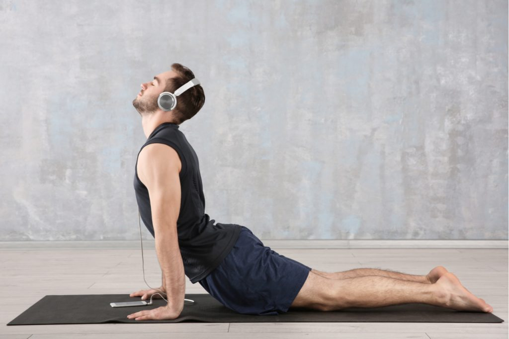 A man enjoying his music while doing yoga.