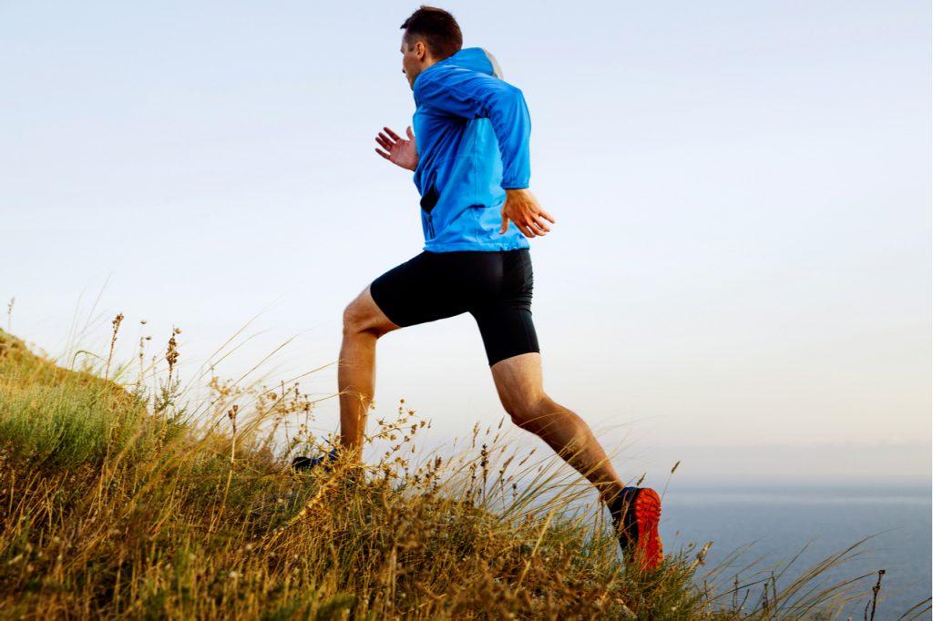 Man athlete running up the mountain.