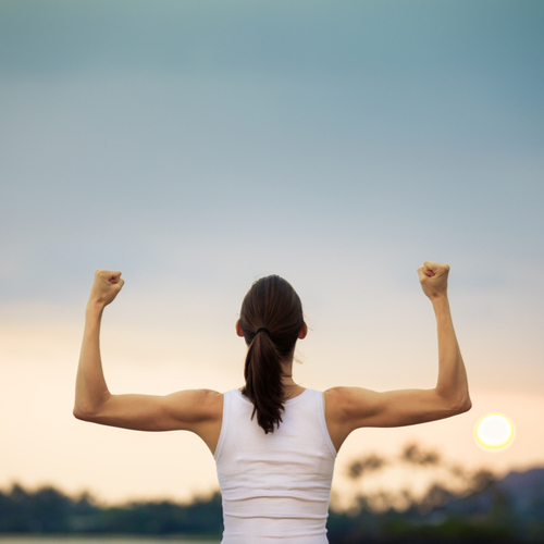 A back of a woman facing the sunset showing positivity by raising her arms like showing her muscles.