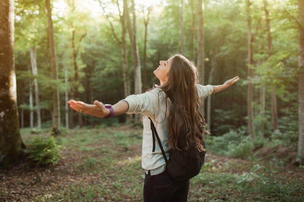 Woman emgracing the sun and nature with backpack in the forest on sunset light in the autumn season, looking up, exploring the nature.