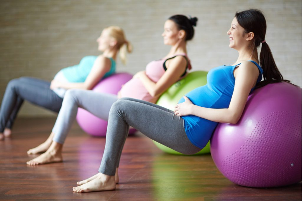 Three pregnant women doing ball exercises.