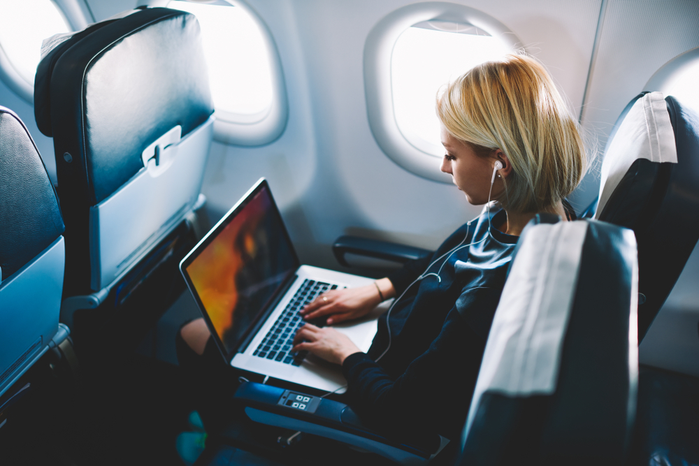 A woman on a plane while working on her laptop.