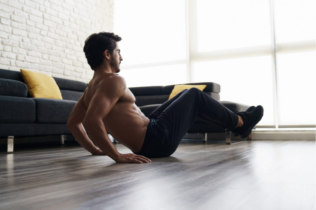 A man performs a knee tuck exercise at home.