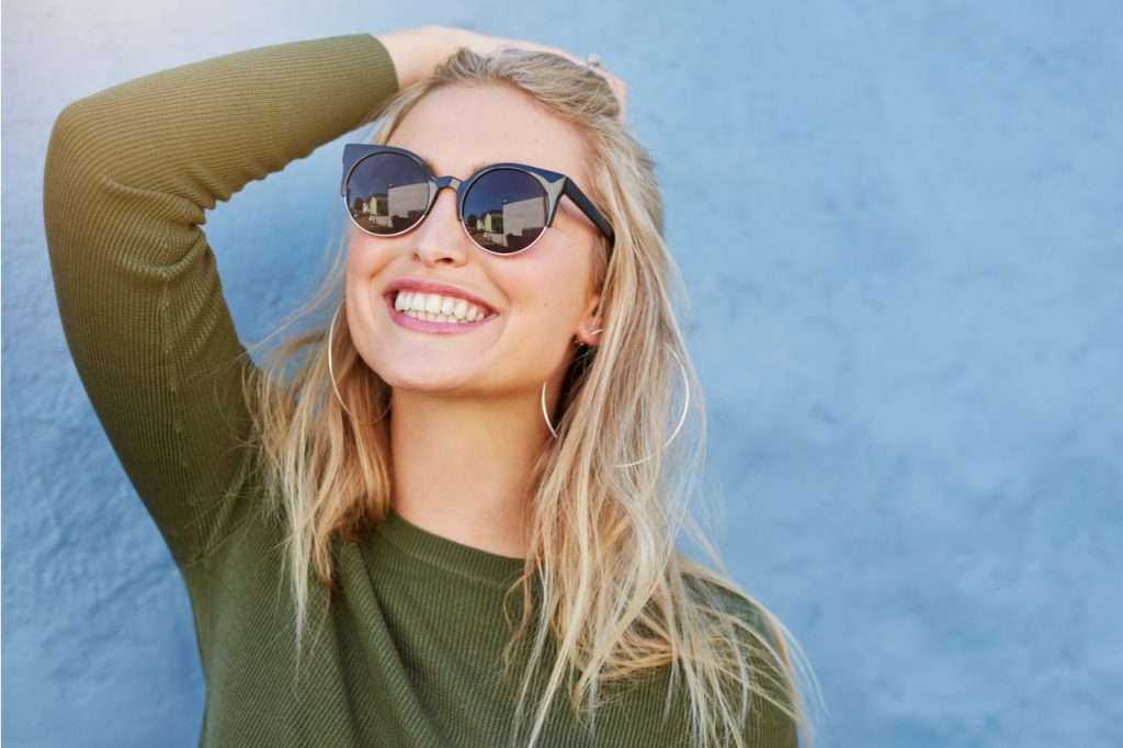 Blonde woman wearing shades smiling, thinking positively.