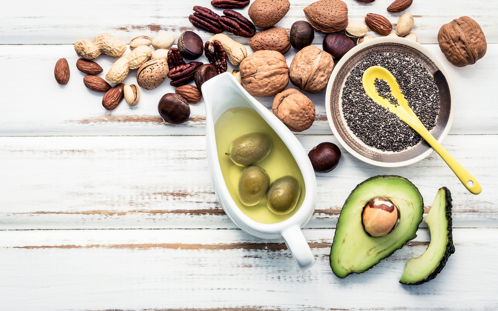 Olives, sliced avocado, a bowl of chia seeds, and variety of nuts.