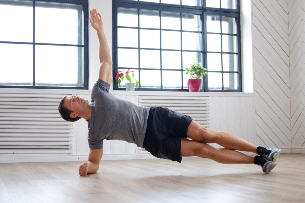 A man doing side plank workout position at home