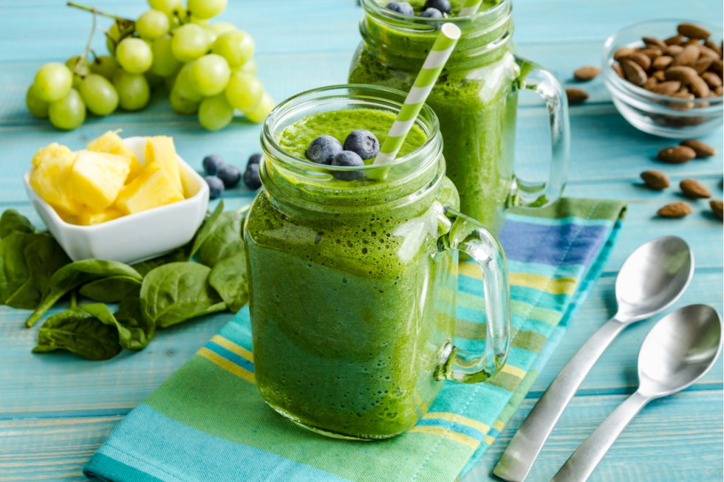 Mason jar mugs filled with green spinach smoothie