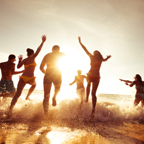 A group of friends having fun at the beach on a sunset.