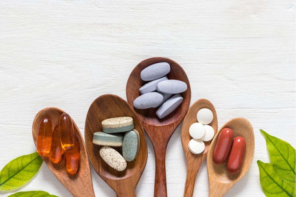 A selection of supplements on 5 different wooden spoons like the alpha brain by onnit.