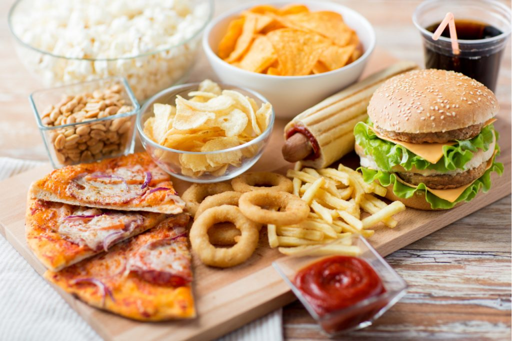 An image of unhealthy food such as burgers, fries, chips, pizza, etc.