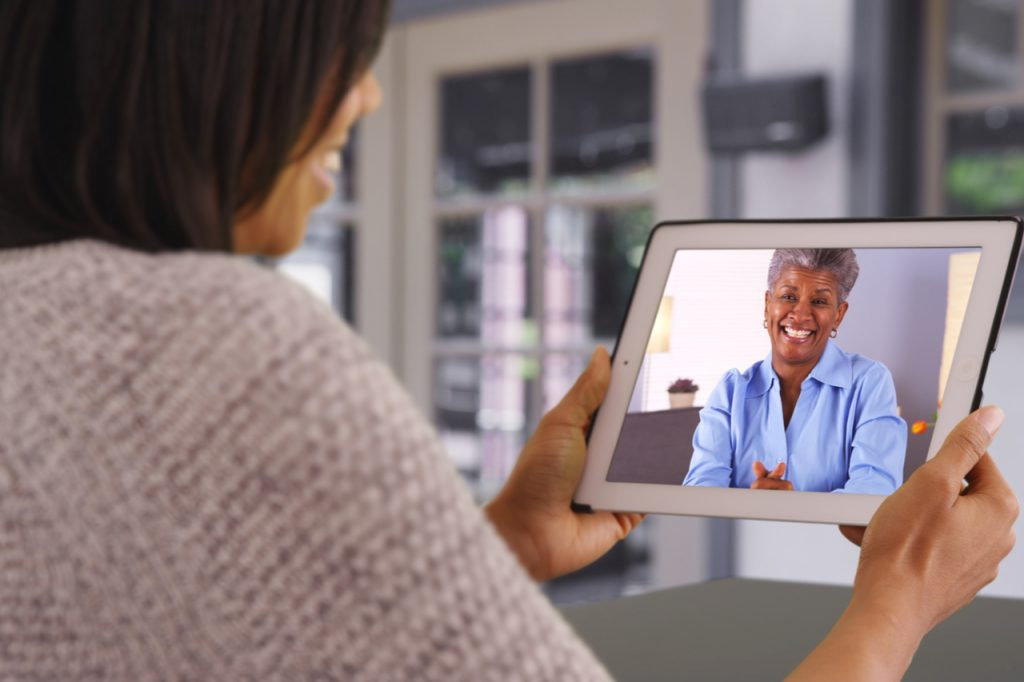 Mother and daughter having a video call using a tablet.