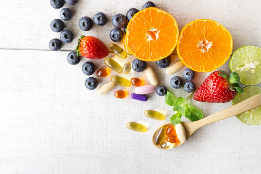 Immunity booster vitamins and supplements with fresh and healthy fruits on white wooden background.