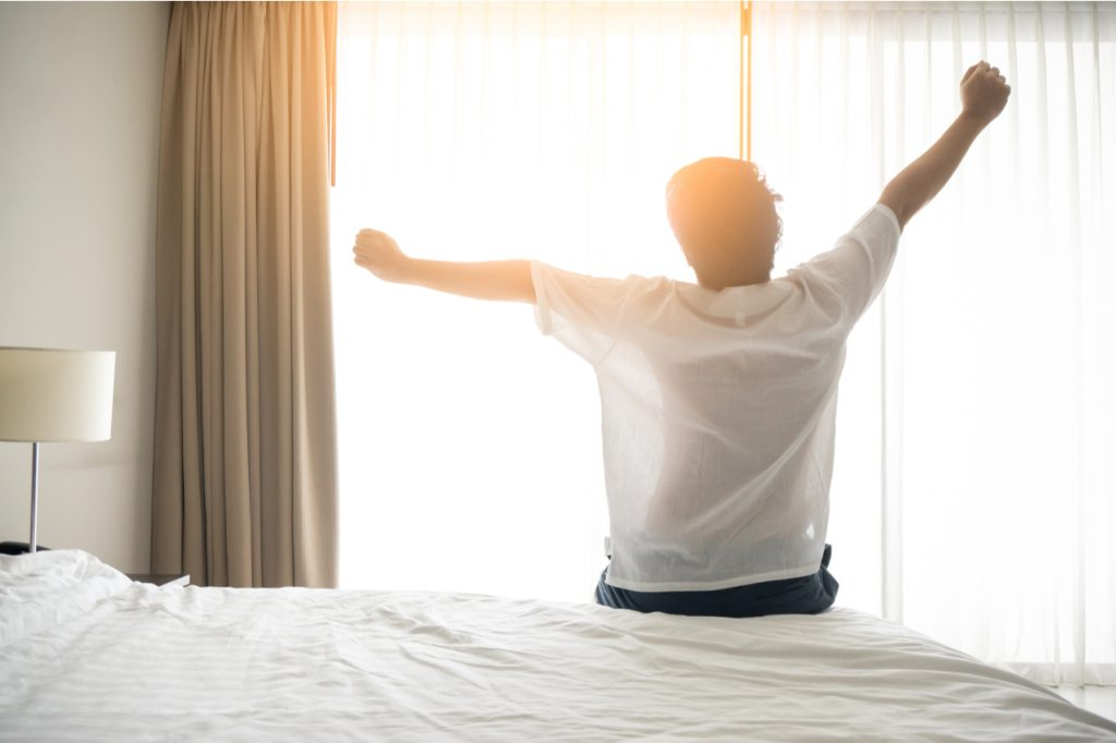 A man raising his hands after waking up early is healthy lifestyle habits.